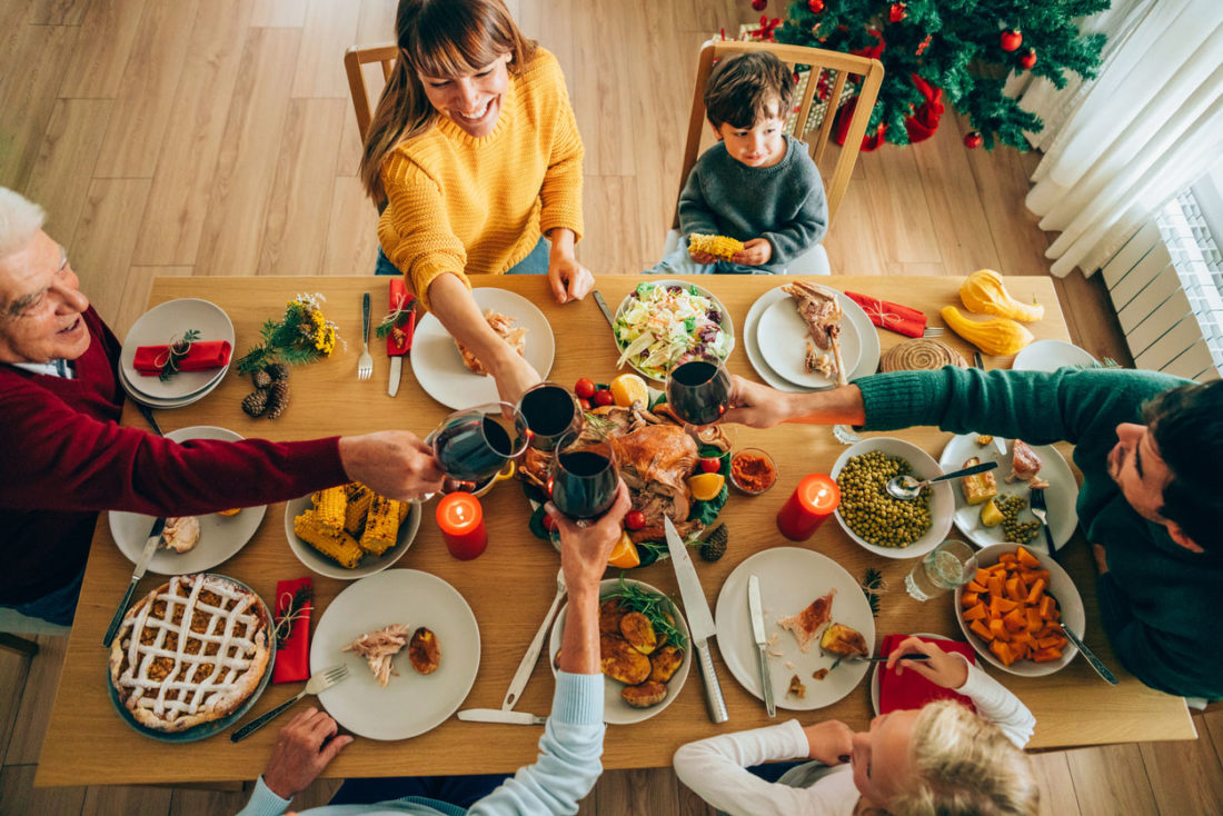 Cheerful family toasting with red wine during Christmas dinner or lunch.