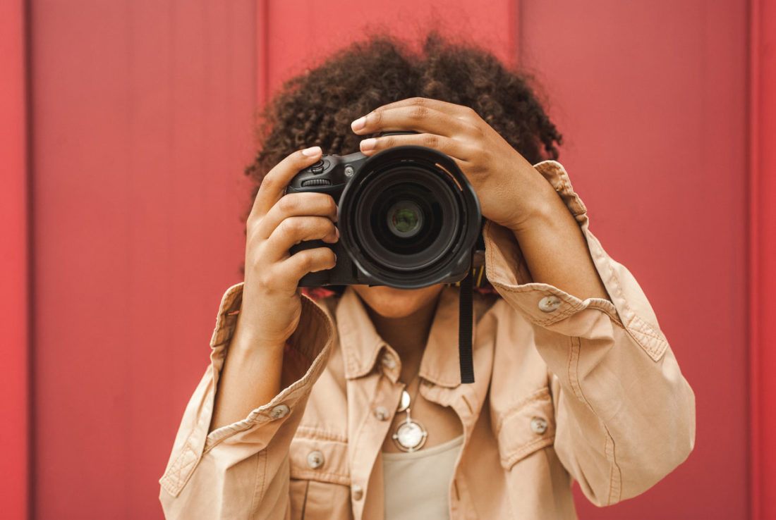 young african american woman using digital camera on street