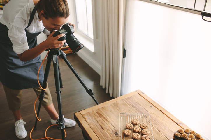Female chef taking pictures of dessert on table with dslr camera mounted on tripod. Female taking pictures of sweet food for her blog.